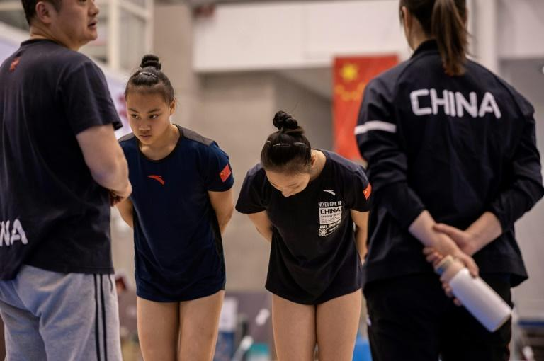 Gymnasts Cheng Shiyi (2nd L) and Yu Linmin (2nd R) bow after being told to improve their technique and motivation during a session at the National Training Centre in Beijing