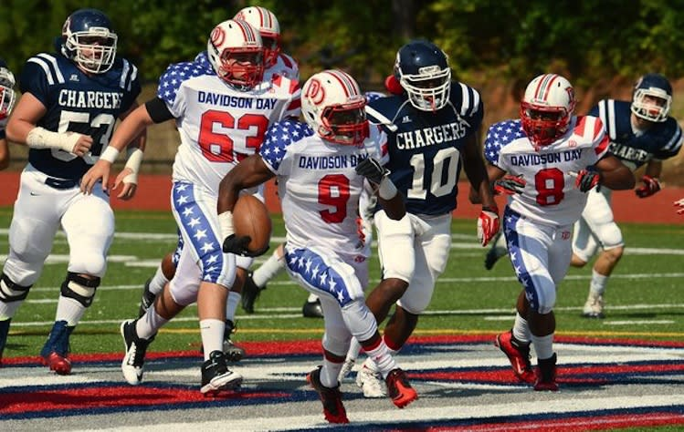Davidson Day running back Jordan Brown (9) shows off the American flag uniforms on a touchdown run -- Charlotte Observer