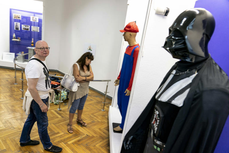 """In this photo taken on Friday, July 12, 2019, visitors walk past a mannequin of Darth Vader, on display in an exhibition at the National History Museum, in Kiev, Ukraine. A Darth Vader costume, playground equipment, pastries and boxes of food all are part of an exhibit at Ukraine's National History Museum displaying the colorful behavior and sometime-questionable practices that characterize the country's elections. The exhibition, called """"The Museum of Election Trash"""" was put together ahead of the  snap parliamentary elections on Sunday, July 21, 2019. (AP Photo/Evgeniy Maloletka)"""
