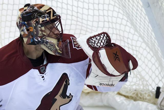 Arizona Coyotes goalie Mike Smith allows a goal to Vancouver Canucks' Brad Richardson during second period NHL hockey action in Vancouver, British Columbia on Monday, Dec. 22, 2014. (AP Photo/The Canadian Press, Darryl Dyck)