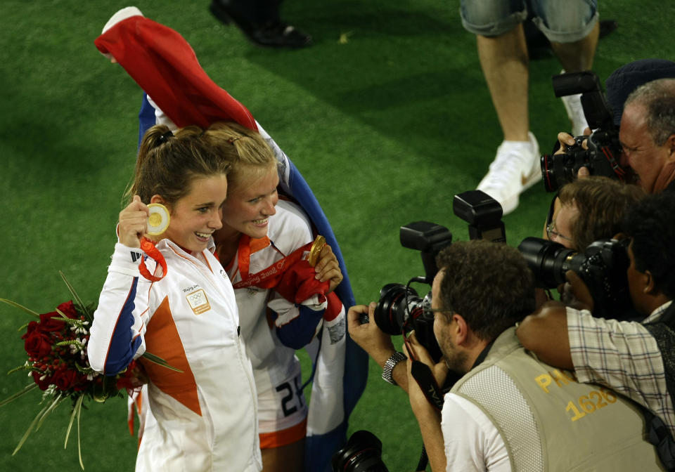 Netherlands' Ellen Hoog, left, and Sophie Polkamp celebrate with their gold medals as photographers take their picture after defeating China 2-0 in the women's gold medal field hockey match at the Olympic Hockey Center at the Beijing 2008 Olympics in Beijing, Friday, Aug. 22, 2008.(AP Photo/Aman Sharma)