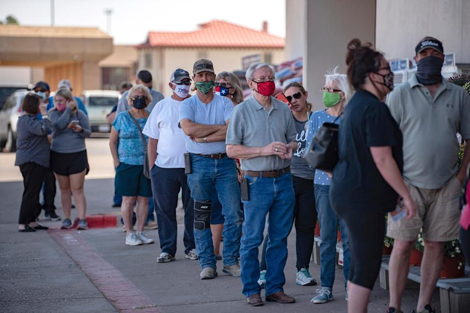 Voters wait in line outside of an Ace Hardware store in Odessa, for the first day of early voting in Texas on Tuesday, Oct. 13, 2020.