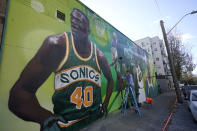"""An artist who goes by the name """"Weirdo"""" puts the finishing touches on a giant mural on an outside wall of Shawn Kemp's Cannabis, the marijuana dispensary owned by Shawn Kemp, a former NBA basketball player for the Seattle SuperSonics and several other teams, and other business partners, Friday, Oct. 30, 2020, prior to the store's grand opening in downtown Seattle. (AP Photo/Ted S. Warren)"""