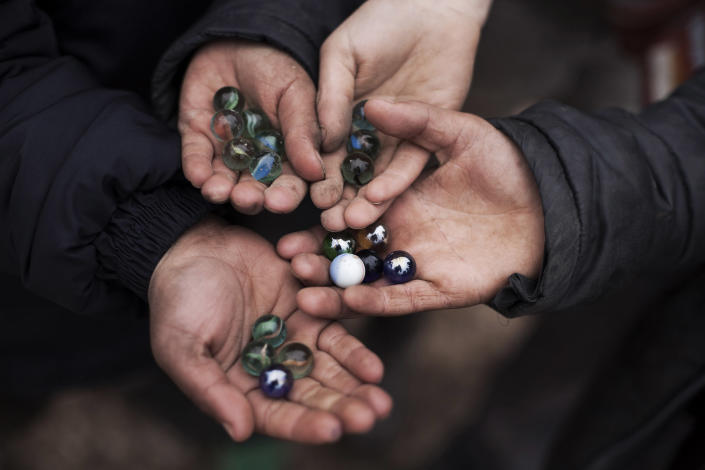 Displaced Syrian children shows their marbles while playing in the Azaz camp for displaced people, north of Aleppo province, Syria, Friday, Feb. 22, 2013. According to Syrian activists the number of people in the Azaz camp has grown by 3,000 in the last weeks due to heavier shelling by government forces. (AP Photo/Manu Brabo)