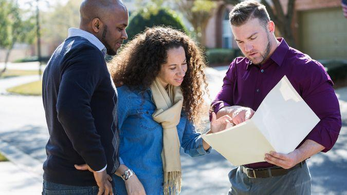 An African American couple standing outdoors on a sunny day on a residential street, with a young man holding a folder.