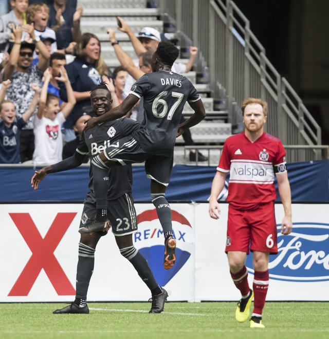 Vancouver Whitecaps' Kei Kamara (23) and Alphonso Davies (67) celebrate Kamara's goal as Chicago Fire's Dax McCarty (6) walks away during the first half of a Major League Soccer match Saturday, July 7, 2018, in Vancouver, British Columbia. (Darryl Dyck/The Canadian Press via AP)
