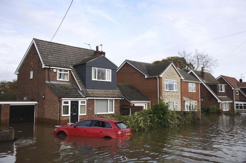 A car submerged in water outside a property as parts of England endured a month's worth of rain in 24 hours, in Fishlake, Yorkshire, England, Monday Nov. 11, 2019. Some scores of people have been forced to evacuate their homes, as flood waters have inundated the region. ( Joe Giddens/PA via AP)