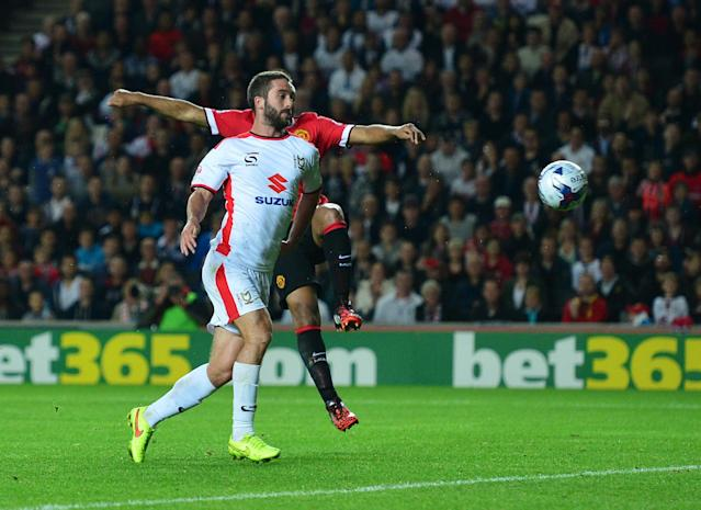 MK Dons Northern Irish striker Will Grigg scores their second goal during the English League Cup second round football match between Milton Keynes Dons and Manchester United at Stadium MK in Milton Keynes, north of London, on August 26, 2014 (AFP Photo/Carl Court )