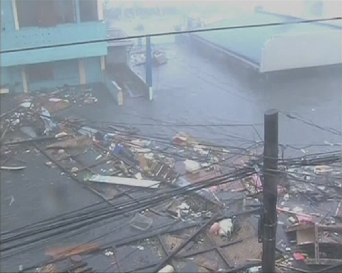Debris float on a flooded road as strong winds and rain continue to batter buildings after Typhoon Haiyan hit Tacloban city, Leyte province in this still image from video November 8, 2013. Haiyan, potentially the strongest recorded typhoon to make landfall, slammed into the Philippines' central islands on Friday, forcing millions of people to flee to safer ground or take refuge in storm shelters. The category-five super typhoon whipped up giant waves as high as 4-5 metres (12-15 feet) that lashed the islands of Leyte and Samar, and was on track to carve a path through popular holiday destinations. REUTERS/ABS-CBN via Reuters TV (PHILIPPINES - Tags: DISASTER ENVIRONMENT) ATTENTION EDITORS - THIS IMAGE WAS PROVIDED BY A THIRD PARTY. FOR EDITORIAL USE ONLY. NOT FOR SALE FOR MARKETING OR ADVERTISING CAMPAIGNS. NO SALES. NO ARCHIVES. THIS PICTURE IS DISTRIBUTED EXACTLY AS RECEIVED BY REUTERS, AS A SERVICE TO CLIENTS. PHILIPPINES OUT. NO COMMERCIAL OR EDITORIAL SALES IN PHILIPPINES