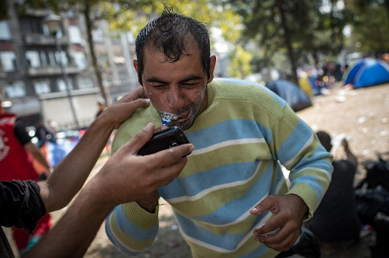 A man shaves at a park where migrants have found temporary shelter in the Serbian capital Belgrade on August 26, 2015 (AFP Photo/Andrej Isakovic)