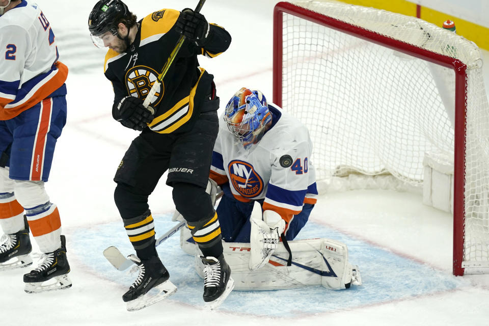 Boston Bruins left wing Jake DeBrusk (74) jumps to allow room for the puck which flies wide of New York Islanders goaltender Semyon Varlamov (40) in the first period of an NHL hockey game, Monday, May 10, 2021, in Boston. (AP Photo/Elise Amendola)