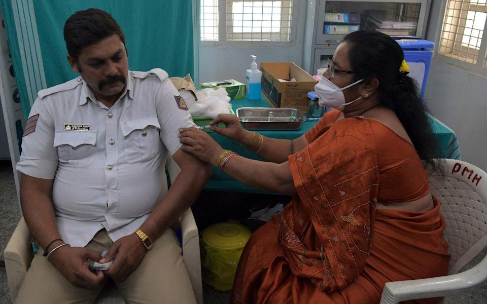 A medical worker inoculates a traffic policeman with a Covid-19 coronavirus vaccine at a hospital in Bangalore - MANJUNATH KIRAN/AFP