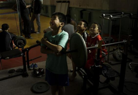 Children watch Mongolia's Olympic freestyle 60kg wrestler Mandakhnaran Ganzorig limber up at a wrestling gymnasium in Ulan Batur October 27, 2011. While the elite of the sporting world tune up for the London Olympics in world class facilities, other gold medal hopefuls are forced to make do with less salubrious surroundings. In Mongolia, Asian champion Ganzorig trains alongside children playing basketball in an old, tired gym with paint peeling from the walls. Children play on ancient free weight machines, climb ropes and roll around on the floor mimicking their wrestling hero as he warms up for his training session in the corner.