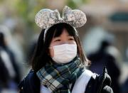 A visitor wearing protective face mask, following an outbreak of the coronavirus, is seen outside Tokyo Disneyland in Urayasu