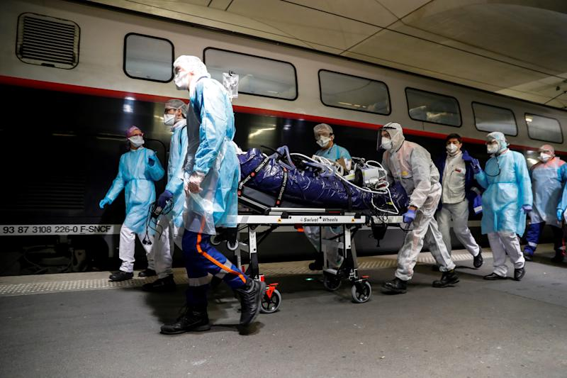 Medics transport a coronavirus patient onto a TGV. (Thomas Samson/Pool via REUTERS)