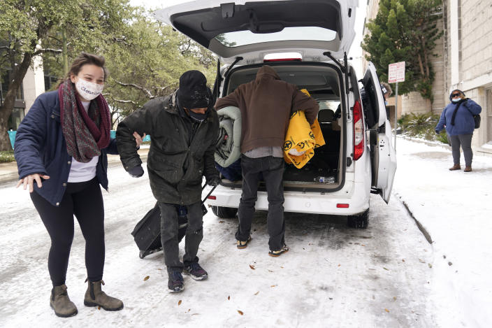 FILE - In this Feb. 16, 2021 file photo, Morgan Handley, left, helps move people to a warming shelter at Travis Park Methodist Church to help escape sub-freezing temperatures, in San Antonio. With the snow and ice clearing in Texas after the electricity was cut to millions as temperatures plunged, people are being found who likely froze to death as they struggled to stay warm in their unheated homes. (AP Photo/Eric Gay, File)