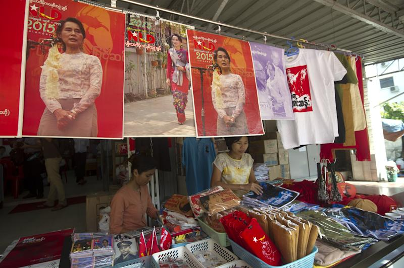 Members of the National League for Democracy work at a souvenir booth beneath posters of Myanmar's opposition leader Aung San Suu Kyi at the party headquarters in Yangon, on November 19, 2014 (AFP Photo/Soe Than Win)
