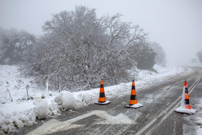 A road with snow is blocked near the Quneitra border crossing between Syria and the Israeli-controlled Golan Heights Wednesday, Feb. 17, 2021. (AP Photo/Ariel Schalit)
