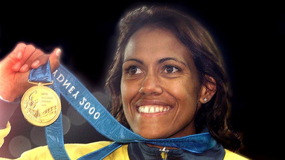 Cathy Freeman smiles while holding up her Sydney Olympics gold medal.