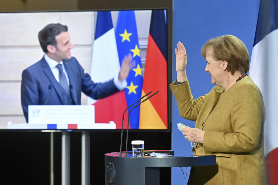 German Chancellor Angela Merkel waves to French President Emmanuel Macron at the end of a press conference following German-French Security Council video talks in Berlin, Germany, Friday, Feb. 5, 2021. (John MacDougall/Pool via AP)