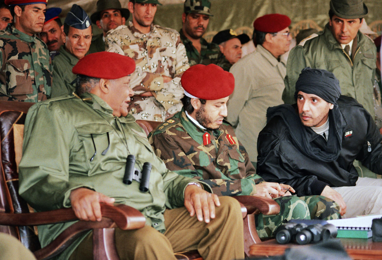 In this undated photo made available Sunday, Sept. 25, 2011, al-Saadi Gadhafi, center, and Hannibal Gadhafi, right, sons of Libyan leader Moammar Gadhafi, are seen in the audience at a military exercise by the elite military unit commanded by their brother, Khamis, in Zlitan - 90 miles (140 kilometers) southeast of Tripoli, Libya. Interpol put ousted Libyan leader Moammar Gadhafi's son al-Saadi on the equivalent of its most-wanted list on Thursday, and said he was last seen in Niger. (AP Photo/Abdel Magid al-Fergany)