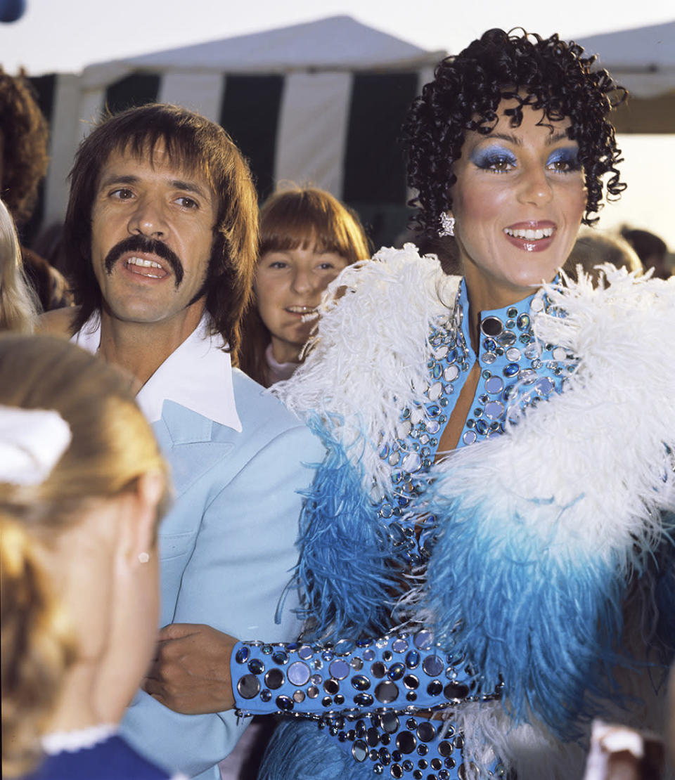 <p>Seen here with Sonny (nice 'stache) in 1978, Cher worked tight curls, bright blue lids, and glossed lips (not to mention feathers and mini-mirrors) to the max. <i>(Photo: Getty Images)</i></p>