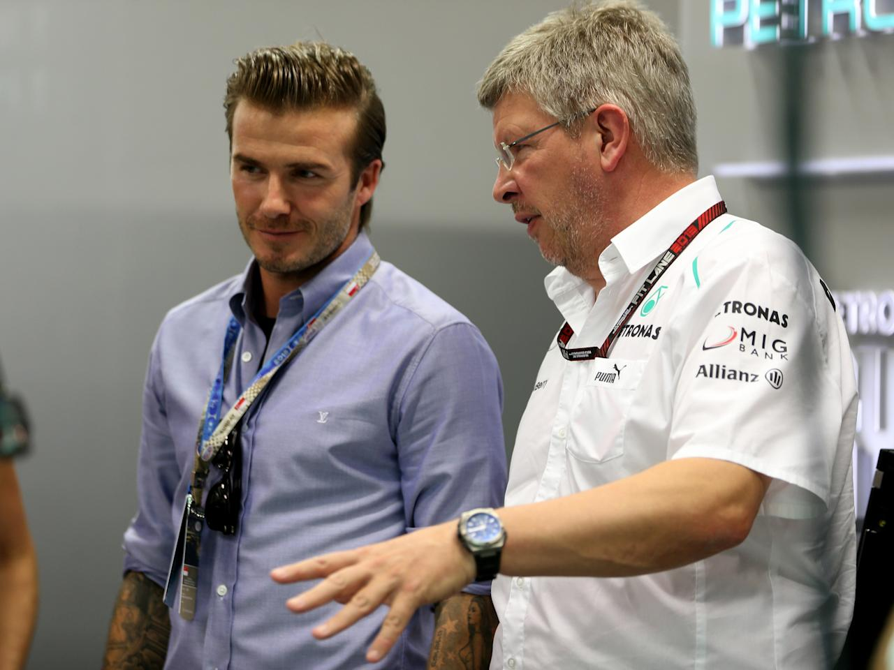 SINGAPORE - SEPTEMBER 22: David Beckham is given a tour of the Mercedes GP team garage by Mercedes GP Team Principal Ross Brawn during the Singapore Formula One Grand Prix at Marina Bay Street Circuit on September 22, 2013 in Singapore, Singapore. (Photo by Mark Thompson/Getty Images)