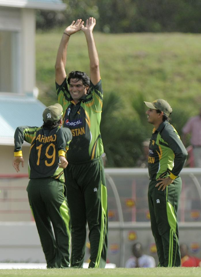 Pakistan bowler Mohammad Irfan (C) waits for a high five from Ahmed Shehzad (L) in celebrates of West Indies batsman Marlon Samuels caught by Umar Akmal as captain Misbah-Ul-Haq (R) looks on July 19, 2013  during the 3rd ODI West Indies v Pakistan at Beausejour Cricket Ground, St. Lucia. Score, Pakistan 229/6, West Indies 229/9, match tied.       AFP PHOTO / Randy Brooks        (Photo credit should read RANDY BROOKS/AFP/Getty Images)