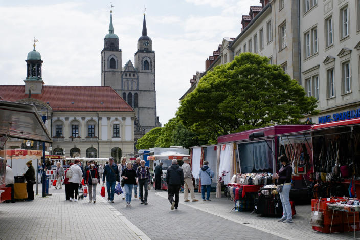 People walk over the market in the federal state Saxony-Anhalt's capital Magdeburg, Germany, Wednesday, June 2, 2021. The state vote on Sunday, June 6, 2021 is German politicians' last major test at the ballot box before the national election in September that will determine who succeeds Chancellor Angela Merkel. (AP Photo/Markus Schreiber)