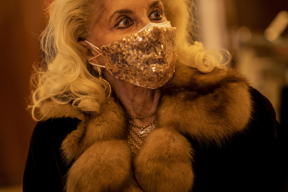 "An opera aficionado, wearing a face mask, walks into the Teatro Real to attend to a performance of ""Rusalka"" in Madrid, Spain, on Thursday, Nov. 12, 2020. The theater is one of the few major opera houses that have reopened during the coronavirus pandemic, although to smaller audiences. (AP Photo/Bernat Armangue)"