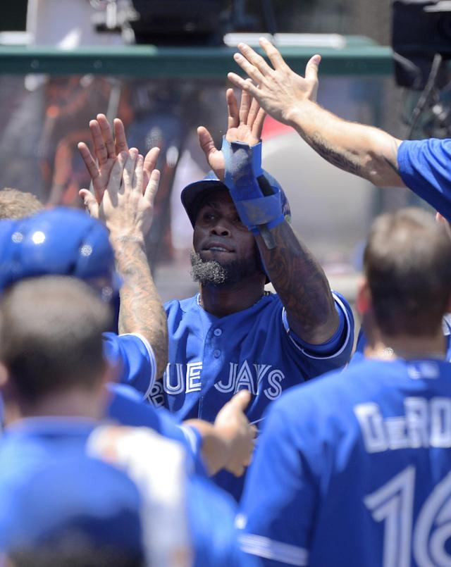 Toronto Blue Jays' Jose Reyes is congratulated after scoring on a single by Rajai Davis during the third inning of their baseball game against the Los Angeles Angels, Sunday, Aug. 4, 2013, in Anaheim, Calif. (AP Photo/Mark J. Terrill)