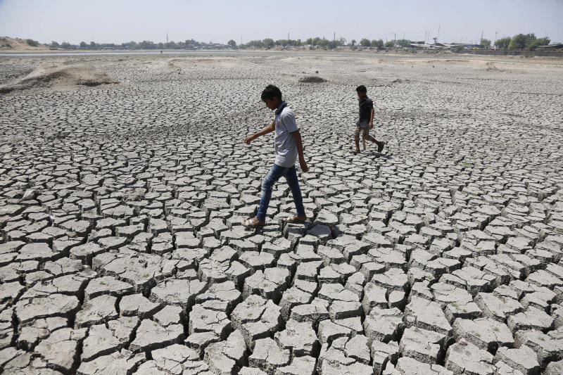 Indian boys walk through a dried patch of Chandola