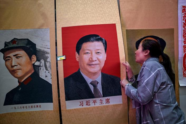 A woman holds a color poster depicting a smiling man next to another poster of a Chinese revolutionary