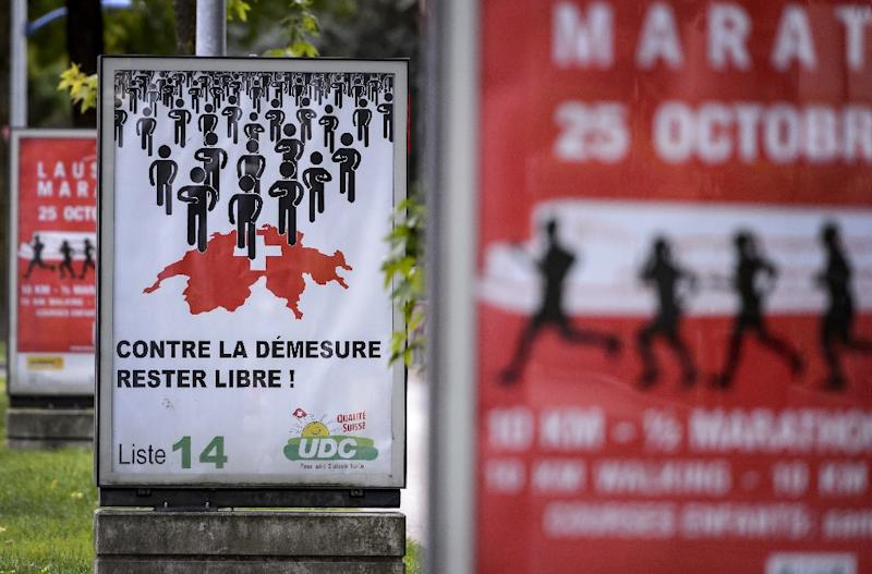 "An electoral poster of the far-right party UDC SVP reading in French ""Against excess, remain free"" is seen between banner of a running sport event in Yverdon, western Switzerland on September 23, 2015 (AFP Photo/Fabrice Coffrini)"
