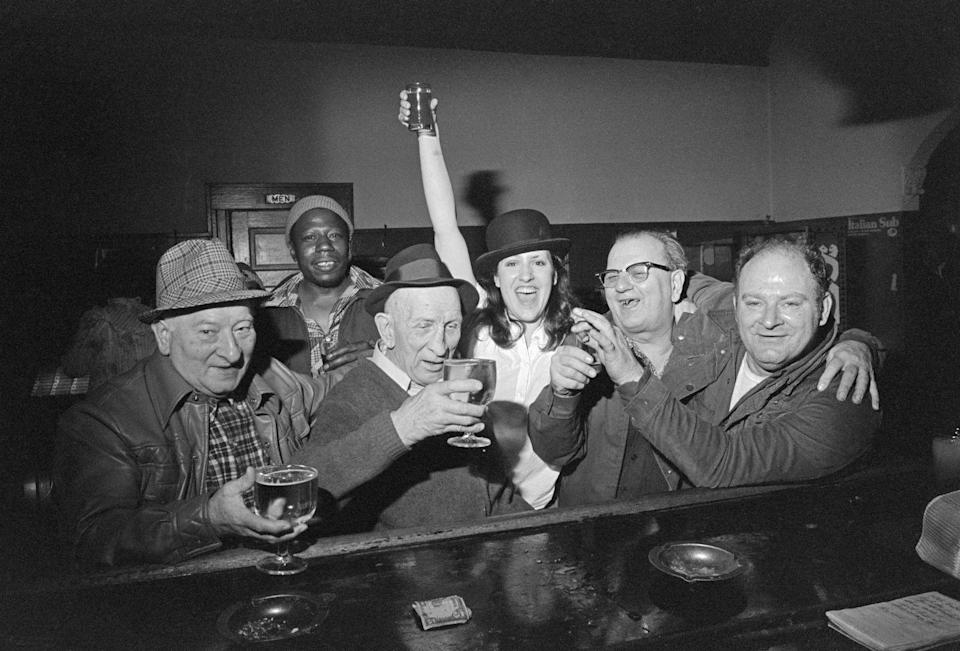 <p>A woman poses with men at a bar in the Poletown neighborhood of Detroit. Named after Polish immigrants who lived in the area, a portion of Poletown became the General Motors plant.</p>