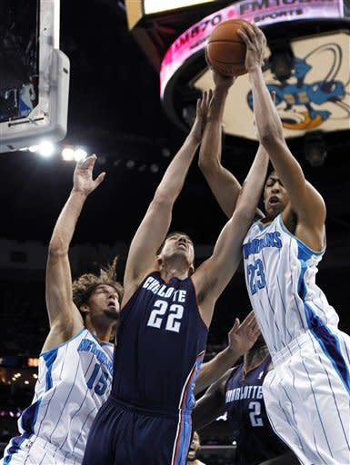 Charlotte Bobcats center Byron Mullens (22) leaps for a rebound against New Orleans Hornets center Robin Lopez (15) and forward Anthony Davis (23) during the first half of an NBA preseason basketball game in New Orleans, Tuesday, Oct. 9, 2012. (AP Photo/Gerald Herbert)
