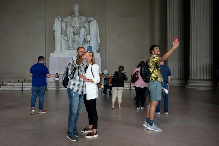 Tourists, some wearing face masks and others unmasked, visit the Lincoln Memorial