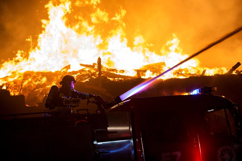 """MINNEAPOLIS, MN - MAY 27: Fire fighters work to put out a fire at a factory near the Third Police Precinct on May 27, 2020 in Minneapolis, Minnesota. A number of businesses and homes were damaged as the area has become the site of an ongoing protest after the police killing of George Floyd. Four Minneapolis police officers have been fired after a video taken by a bystander was posted on social media showing Floyd's neck being pinned to the ground by an officer as he repeatedly said, """"I can't breathe"""". Floyd was later pronounced dead while in police custody after being transported to Hennepin County Medical Center. (Photo by Stephen Maturen/Getty Images) (Photo: Stephen Maturen via Getty Images)"""