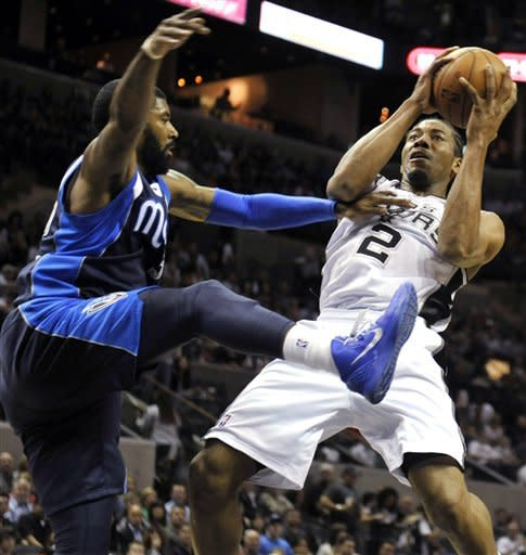 San Antonio Spurs forward Kawhi Leonard (2) is fouled on a shot attempt by Dallas Mavericks guard O.J. Mayo during the first half of an NBA basketball game, Thursday, March 14, 2013, in San Antonio. (AP Photo/Bahram Mark Sobhani)
