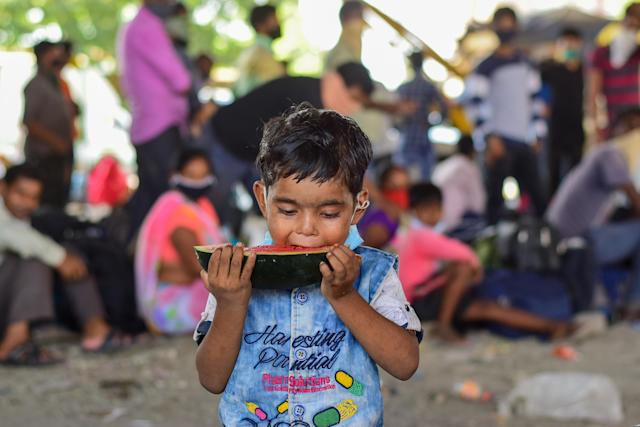 MUMBAI, MAHARASHTRA, INDIA - 2020/05/13: A boy eats a piece of watermelon as they wait to board vehicles during the stranded situation. Due to lockdown situation, most migrants are stuck in Mumbai, some walk and others arrange their own trucks and buses to their home towns, while the police say that the buses are available by the government. (Photo by Ratika More/SOPA Images/LightRocket via Getty Images)
