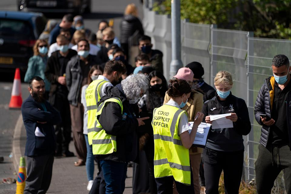<p>People queue for vaccines in Bolton</p> (AP)