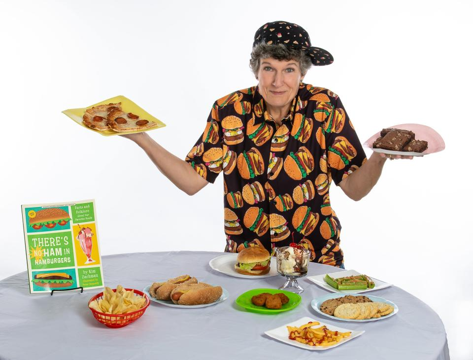 """This photo shows Kim Zachman posing with her book and plates of food on Oct. 5, 2020, in Roswell, Ga. Zachman's book for young readers, """"There's No Ham in Hamburgers,"""" offers kids ages 8 to 12 a fun-filled journey through the history of some of their favorite foods. (Cloud8photo.com via AP)"""