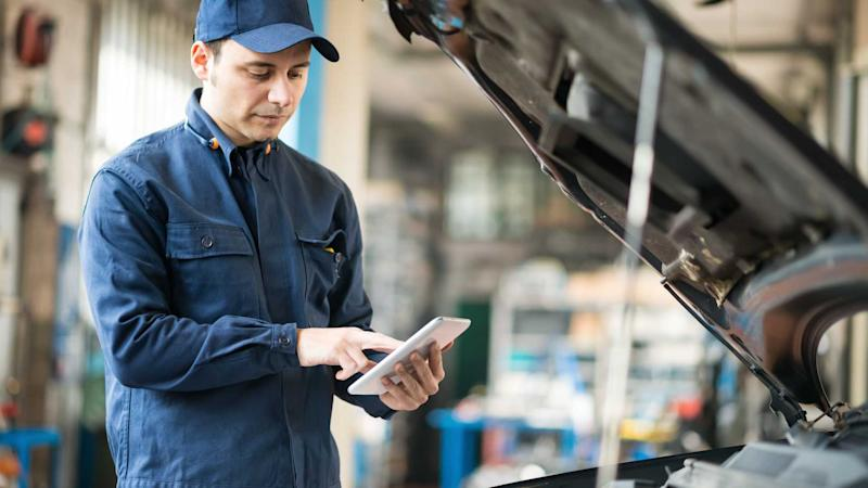 Mechanic using a tablet to perform MOT inspection