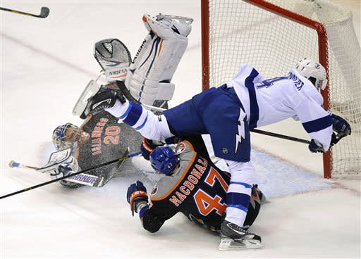 Tampa Bay Lightning's Vincent Lecavalier (4) collides with New York Islanders goalie Evgeni Nabokov (20) and Islanders' Andrew MacDonald (47) in the first period of an NHL hockey game Saturday, April 6, 2013, at Nassau Coliseum in Uniondale, N.Y. (AP Photo/Kathy Kmonicek)