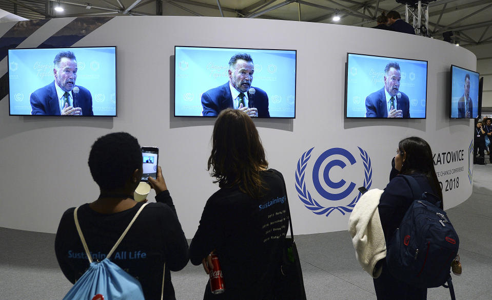 Visitors to the U.N. climate conference watch a speech by Arnold Schwarzenegger, in Katowice, Poland, Monday, Dec. 3, 2018. The COP24 UN Climate Change Conference is taking place in Katowice, Poland. Negotiators from around the world are meeting for talks on curbing climate change. (AP Photo/Czarek Sokolowski)