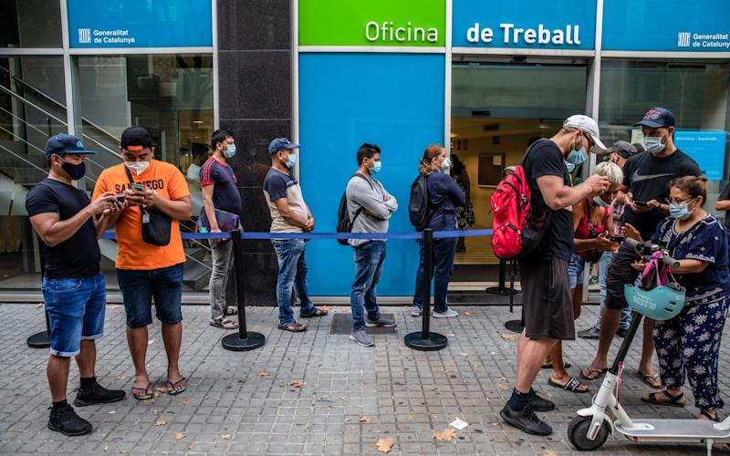 Job seekers try to access an online appointment system on their mobile phones as people queue outside a regional employment office in Barcelona, Spain, on Wednesday, Aug. 12 - Angel Garcia/Bloomberg