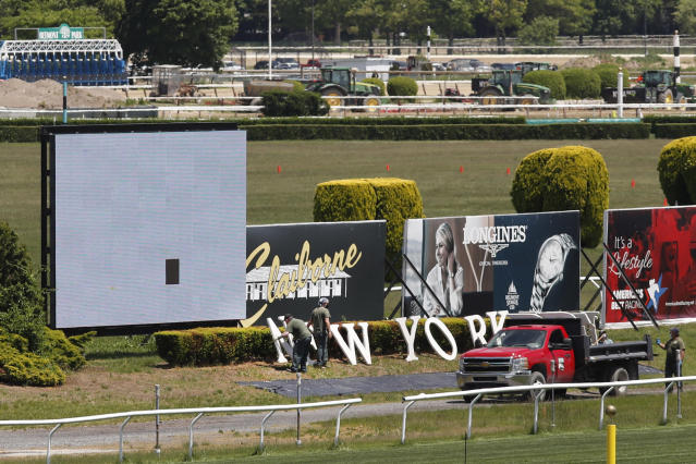 """Workers place letters spelling out '\""""New York"""" on the infield at Belmont Race Track as they prepare for the 2020 Belmont Stakes race, which this year will be the first leg of horse racing's Triple Crown, Wednesday, May 27, 2020, as Phase One reopening plans were put into action in Elmont, N.Y. Belmont is usually the last leg of horse racing's Triple Crown, but this year it will be held first. Normally held in early June, the race has been rescheduled to June 20, 2020, and will be run without spectators in attendance. (AP Photo/Kathy Willens)"""