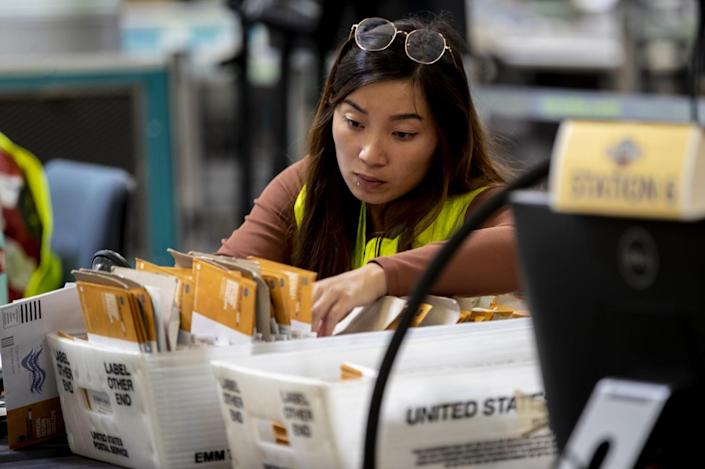 An election worker verifies signatures on mail-in ballots