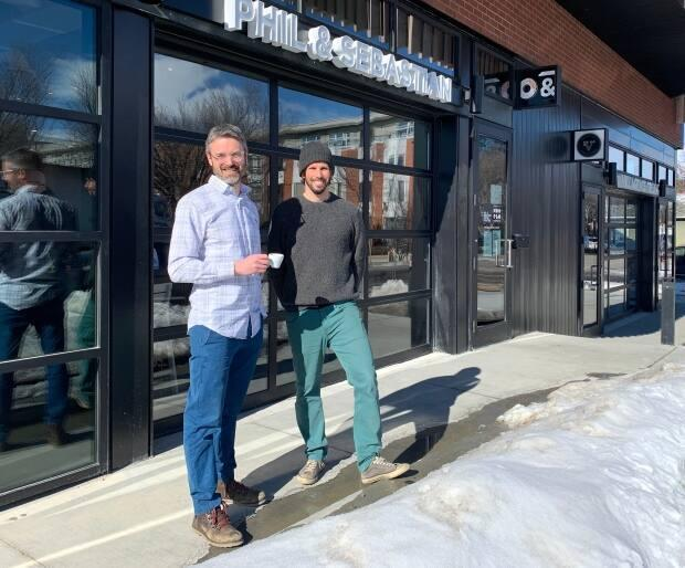 Phil Robertson and Sebastian Sztabzyb stand outside the newest location of their locally owned coffee shop, Phil &Sebastian. They decided to open during the pandemic despite the loss of sales and employees over the past year at their other locations.  (Bryan Labby/CBC - image credit)