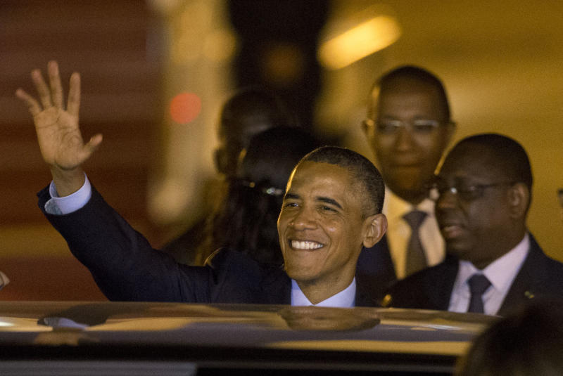 U.S. President Barack Obama waves as he boards a car after arriving at the airport in Dakar, Senegal, Wednesday, June 26, 2013. Seen right is Senegalese President Macky Sall. President Obama opened a weeklong trip to Africa on Wednesday, a three-country visit aimed at overcoming disappointment on the continent over the first black U.S. president's lack of personal engagement during his first term. (AP Photo/Rebecca Blackwell)